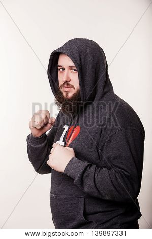 Boxer with a serious face with a huge beard. In the hood stands hands clenched into fists before the fight. Isolated on white background