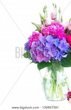 Bright fresh pink peony, eustoma and blue hortensia flowers bouquet in vase close up isolated on white background
