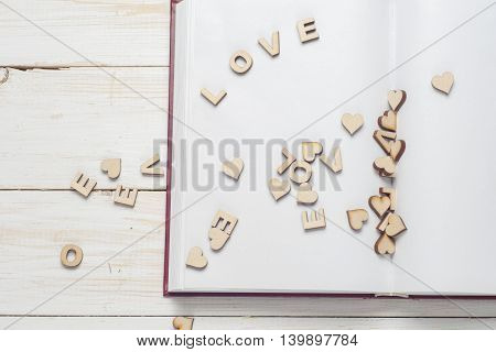 The Word Love A Lot Of Hearts On A Background Of Book On A Wooden Table. Back To School Copy Space.