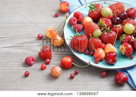 Ceramic plate of assortment berries strawberries raspberries cherries at old wooden table. Close up high resolution product. Harvest Concept
