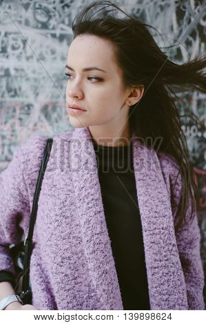 beautiful young model posing near the wall in the city