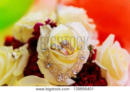 Wedding rings closeup on a pattern background golden romance