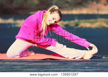 Young girl train in park stretching. Exercises to keeping shape. Taking care about healthy lifestyle and slim figure.