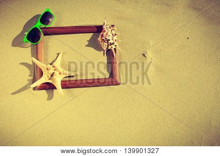 Summer photos concept. Frame on sand on the beach. Seashells and sunglasses lying on the seashore by the sea.