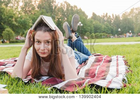 Young Woman with Book at Park Lying on Grass. Education Concept