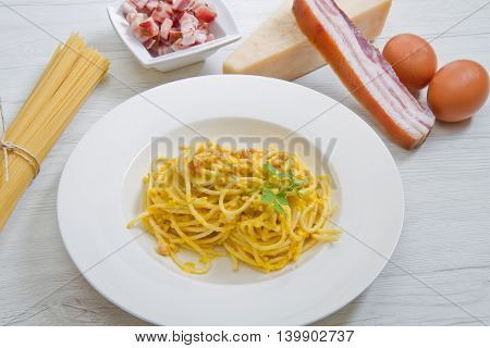 dish with carbonara's spaghetti and ingredients on white wood