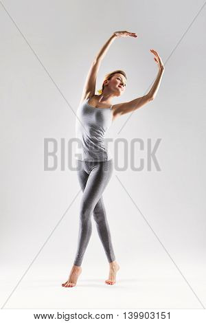 Sporty beautiful ballet dancer woman posing on a studio background