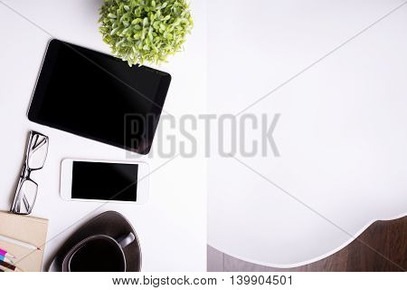 Top view of light office desktop with blank pad cellular phone glasses coffee cup plant and stationery items. Mock up