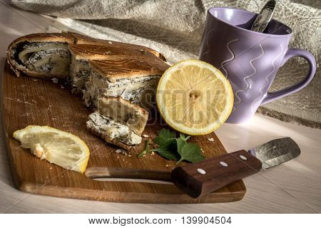 Cheese pie with spinach on a Board, a lemon, a Cup of tea