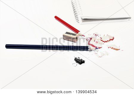 Closeup of white desktop with pencils sharpener sawdust small peg and spiral notepad