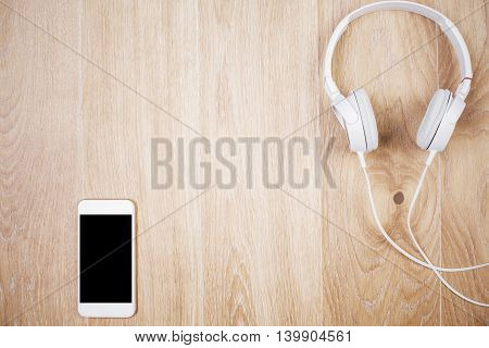Top view of wooden table with blank mobile phone and headphones. Mock up