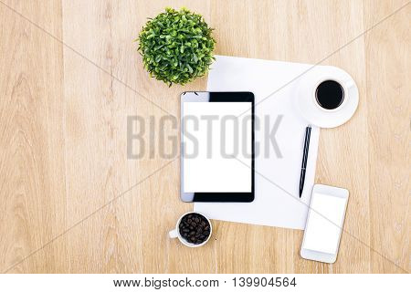 Top view of wooden desktop with blank white tablet smartphone coffee cups paper sheet pen and decorative plant. Mock up