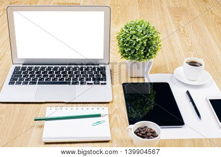 Front view and closeup of creative designer workplace with blank white laptop decorative plant spiral notepad coffee cups tablet smartphone and other items. Mock up