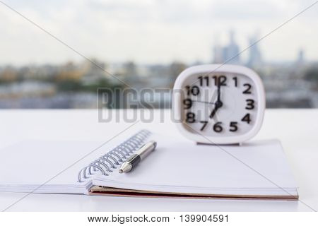 Closeup of open spiral notepad pen and clock on blurry city background