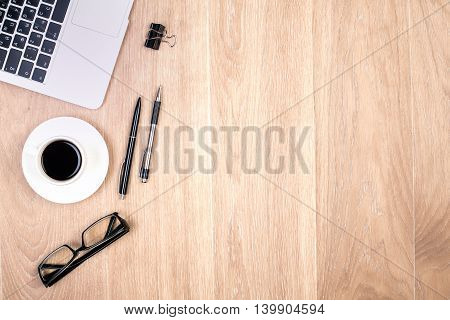 Top view of wooden desktop with coffee cup glasses two pens small peg and laptop keyboard. Mock up