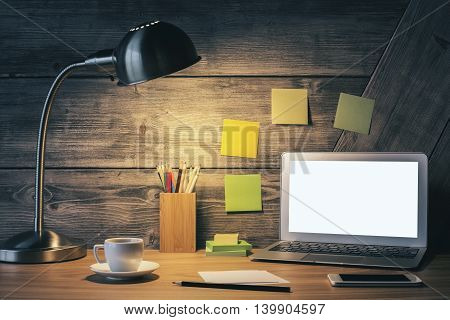Creative desk with blank white laptop table lamp coffee cup smart phone and other items. Mock up