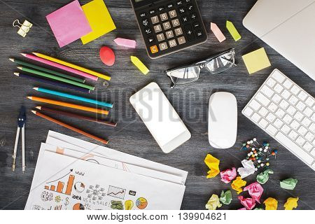 Creative messy office desktop with blank white cellular phone glasses computer mouse keyboard calculator business sketch crumpled paper balls and various stationery items. Mock up