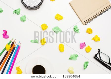 Messy office desktop with colorful crumpled paper pieces coffee cup pencils glasses notepad and clock. Top view Closeup
