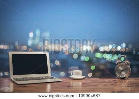 Front view of creative designer desktop with blank laptop silver alarm clock and coffee cup on blurry night city background. Mock up