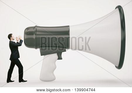 Tiny businessman screaming into huge loudspeaker on light background. Communication concept. 3D Rendering