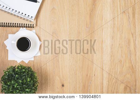 Wooden office desktop with coffee cup spiral notepads and plant on its left side. Mock up