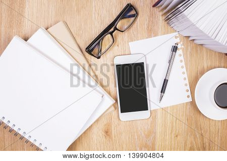 Top view and close up of wooden office desktop with blank spiral notepad mobile phone glasses coffee cup book pages and stationery items. Mock up