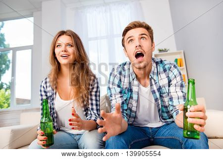 Portrait Of Excited Couple In Love Watching Football With Beer