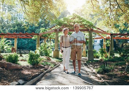 Happy Senior Couple Walking Together In A City Park