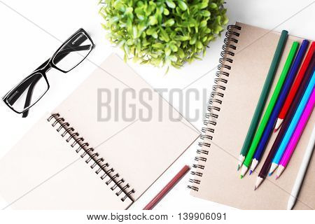 Top view of white desktop with blank spiral notepad glasses plant and colorful pencils. Mock up