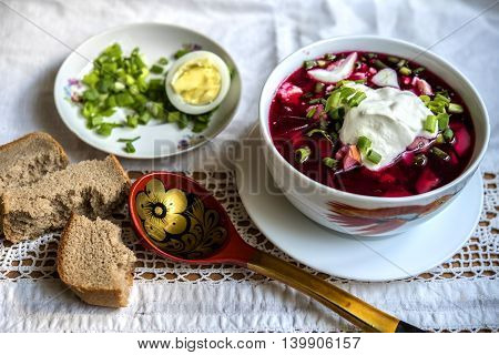 Beet soup, onion, bread, egg, wooden spoon, sour cream