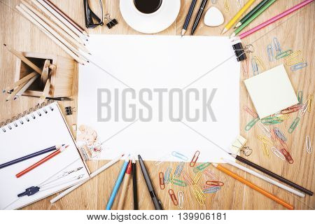 Wooden desktop with blank paper colorful supplies and coffee cup. Mock up