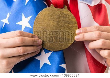 Athlete shows gold medal and holding the flag of USA