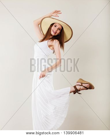Holidays and summer fashion. Woman wearing big straw hat white dress. Female model posing on bright gray background.