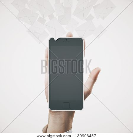 E-mail marketing concept with hand holding blank smartphone with abstract letters on light background. Mock up 3D Rendering