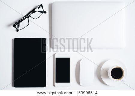 Top view of bright desktop with blank tablet smartphone coffee cup closed laptop computer mouse and glasses. Mock up