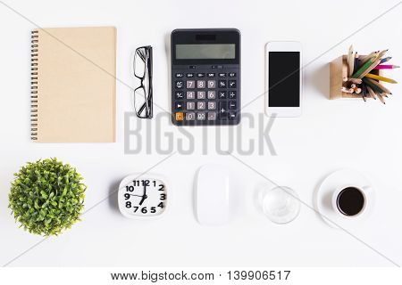 Top view of light office desktop with blank spiral notepad glasses smartphone calculator decorative plant coffee cup computer mouse pencils clock and water glass. Mock up