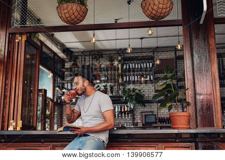 Happy Young Man At Cafe With A Book And Drinking Coffee