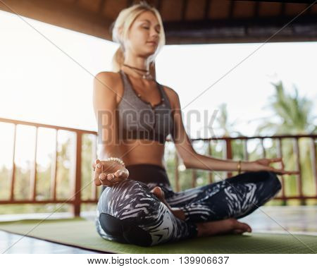 Woman Meditating In Lotus Pose At Health Center