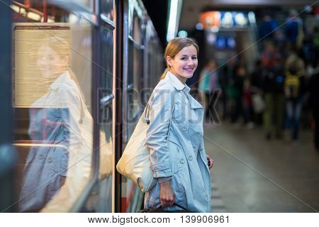 Elegant, smart, young woman taking the metro/subway