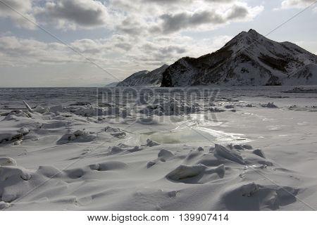 the rocks along the shore of a frozen sea