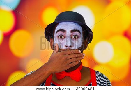 Headshot pantomime man with facial paint posing for camera using hands to cover mouth, blurry lights background.