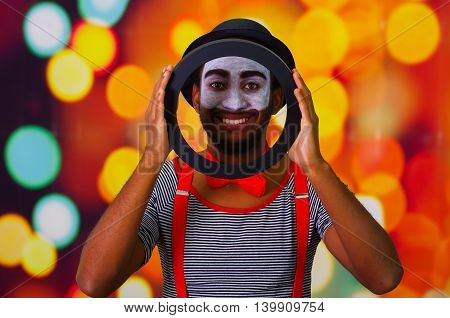 Pantomime man with facial paint posing for camera holding circle showing face in middle, blurry lights background.