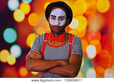 Pantomime man wearing facial paint posing for camera, standing with arms crossed, blurry lights background.