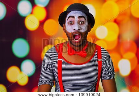 Pantomime man wearing facial paint posing for camera interacting making funny expressions, blurry lights background.
