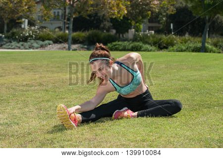 Attractive teen athlete stretching her hamstrings on the grass.