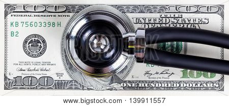 Medical costs concept with stethoscope and paper currency.