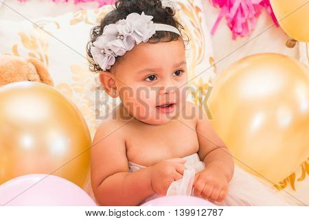 Cute Baby Girl Sitting With Pillows and Balloons