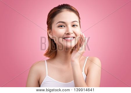 Portrait of attractive Vietnamese woman touching her face on pink background.