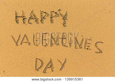 Happy Valentines Day - hand-drawn in gentle sea beach sand.