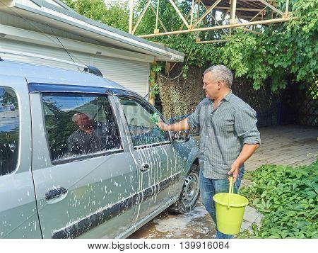 Man washing his silver car near the house.